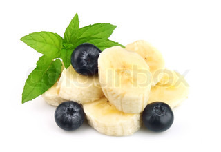 Segments of a banana with berries of a bilberry and mint on a white background