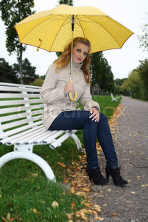 Happy woman with yellow umbrella sitting on bench