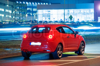 Side view of red car in the city, near the airport at night, Riga, Latvia