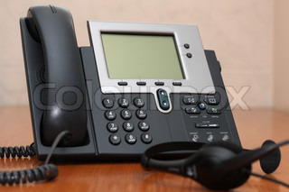 IP Phone close-up view with blurred headset on foreground