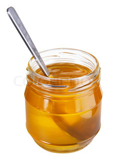 Jar of honey with spoon isolated on white