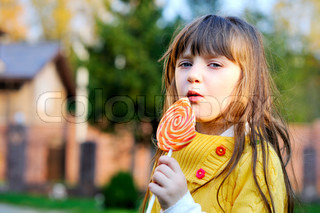 Portrait of cute little girl eating big lollipop on a stick outdoors