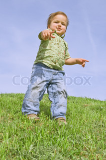 A child pointing at camera, against blue sky
