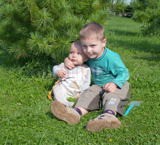 Little girl and boy sitting on the grass