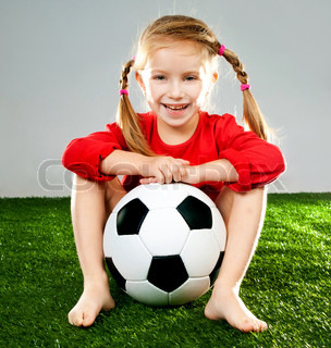 little girl with soccer ball in boots on a green lawn