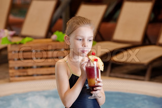 Happy little girl relaxing by the pool with glass of coctail
