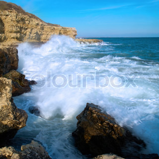 Big waves breaking on the shore with sea foam