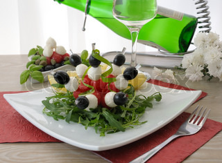 Mozzarella with cherry tomatoes and olives on a skewer with arugula and white wine