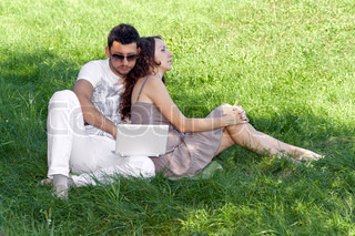 Man with laptop and woman sitting on the grass in the park