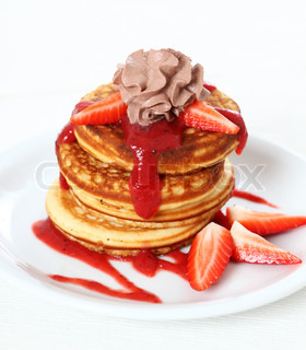 Sweet pancakes with strawberry sauce and chocolate cream