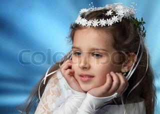 Erstkommunion schönes Mädchen im weißen Kleid