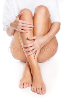 Close up of slender naked legs being massaged isolated on white - healthcare and beauty concept