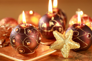 Christmas still life with candles and jingle bells in brown and golden tone