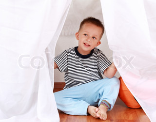Adorable boy playing hide-and-seek at home