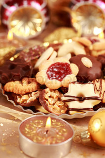 Detail of delicious Christmas cookies with candles in golden tone