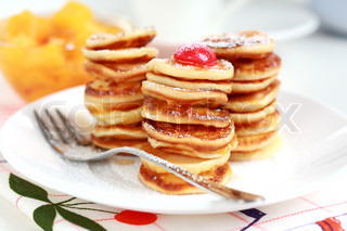 Sweet pancakes with compote and pancake maker background