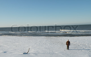 single man going on snowy beach with foaming waves in background