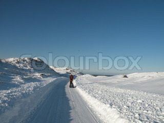 man pulling sleigh with girl through snow covered dune and way with blue sky and north sea in background