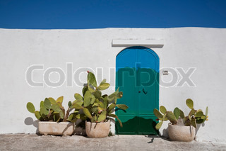Nice painted door and wall in the Apulian town Ostuni, Italy on a hot September day with a nice blue sky