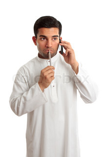 Worried troubled thinking mixed race ethnic man on a telephone callHe is dressed in middle eastern south asian clothing