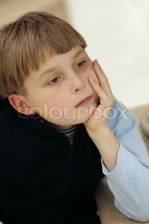 Child sitting quietly and pondering Shallow dof