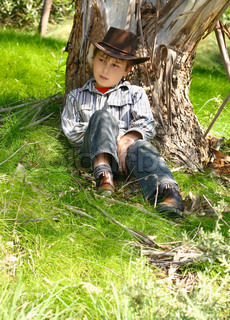 A boy from the bush sits under the shade of an Australian gum tree