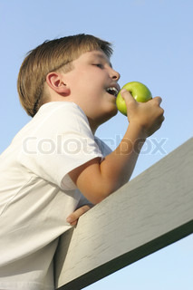 Boy outdoors in afternoon light by a fence eating a juicy green apple 