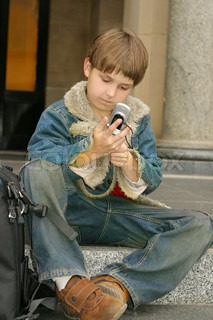 Schoolboy in jeans and a denim jacket sitting on school steps with a cellphone mobile phone