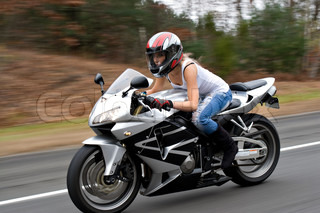 A woman drives a motorcycle at highway speeds with motion blur visible in the background