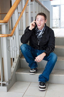 A young man stops to sit on the stairs and talk on his cell phone