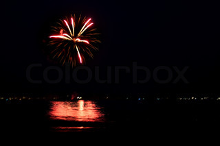 Beautiful fireworks going off over the dark night sky reflecting over the water