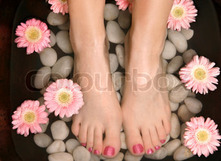 Female feet in a relaxing aromatic foot bath with massaging white stone pebble bed and floating pink flowerheadsFeet are invigorated, skin is supple and refreshed