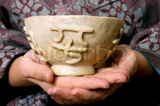 A woman's hands holding a natural antique jade bowl with four chinese heiroglyphs carved into the bowlThe four chinese characters translated say