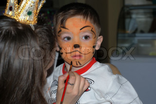 Small boy 3 years old with tiger make-up