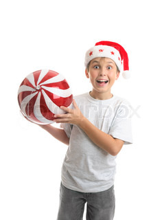 An excited ecstatic boy holding a big Christmas bauble ball decorationRed and white with sparkling glitter and a silver thread