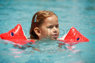 Small girl swimming in pool with water wings
