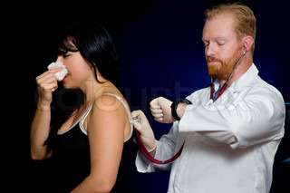 A patient receives a checkup by her doctorFocus on hands and stethoscope