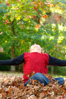 A boy throwing autumn leaves into the airMotion