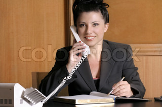 Professional business woman at work desk on the phone