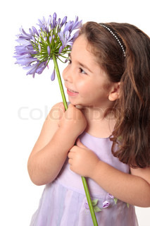 Pretty littlegirl in purple mauve dress holding a beautiful agapanthus flower and smiling sweetlyShe is ooking sideways at your slogan or text