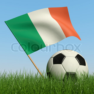 Soccer ball in the grass and the flag of Ireland against the blue sky
