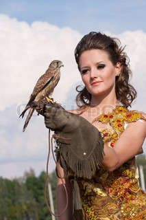 The woman in a beautiful old style dress with falcon has a rest before hunting in yellow field