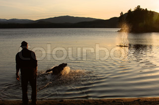 A man throws a stick into the water and a dog get it back