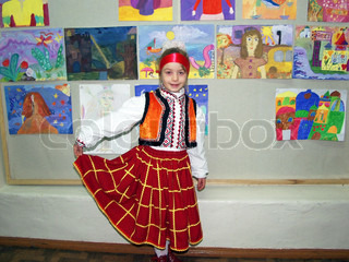 A young schoolgirl in traditional dress against a wall with children's drawings