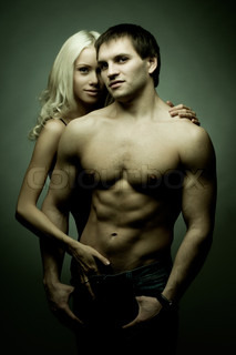 muscular handsome sexy guy with pretty woman on dark background, look on camera, glamour green light