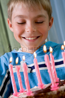 boy holding a cake with candles on birthday