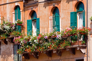 Italian balcony with beauty flowerpots and flowers