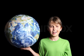 A young boy holding the earth world ball in his hand against a black background