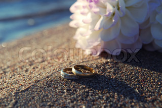 Gold wedding ring in the sand near the water at the beach Next to the ring is a white flower