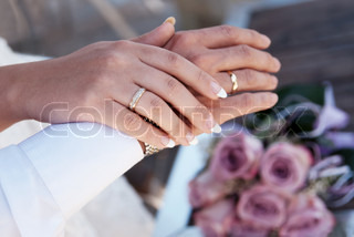 Male and female hands with wedding rings In the background, wedding bridal bouquet